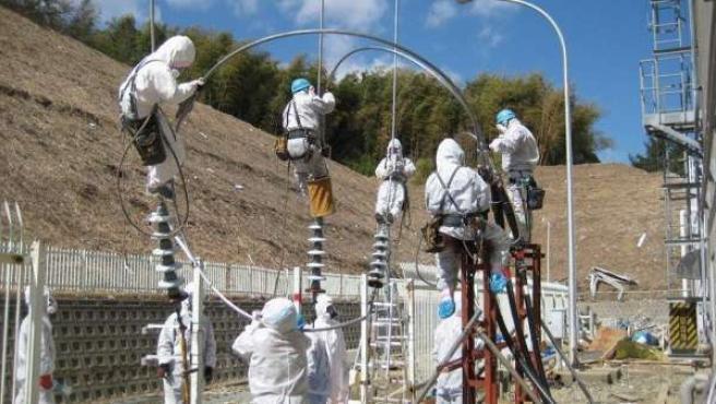 Fotografía facilitada por la empresa operadora de la central nuclear de Fukushima Daiichi, TEPCO, que muestra a sus trabajadores vestidos con monos especiales mientras trabajan.