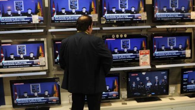 Un hombre mira el vídeo sobre un comunicado anterior de ETA en una tienda de Bilbao.