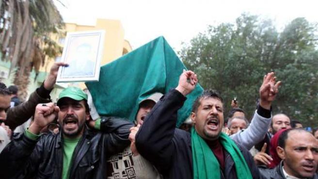 Manifestantes libios sostienen el féretro de Mondher El Mahdi El Daas, fallecido el pasado domingo en Sirte por un ataque de la coalición.