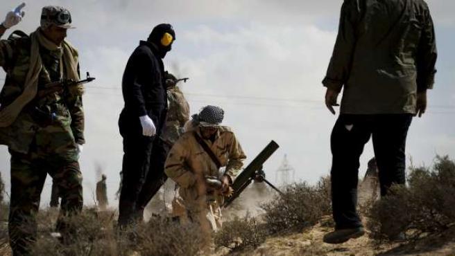Milicianos rebeldes libios disparan un mortero junto a una carretera entre Brega y Ajdabiya.