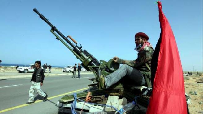 Un rebelde libio vigila encima de un vehículo militar, mientras guarda su posición en una carretera próxima a Ben Yauad.