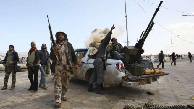 Rebeldes libios defienden su posición mientras son atacados por las fuerzas aéreas libias, leales al líder libio Muamar al Gadafi, en Ras Lanuf, Libia.