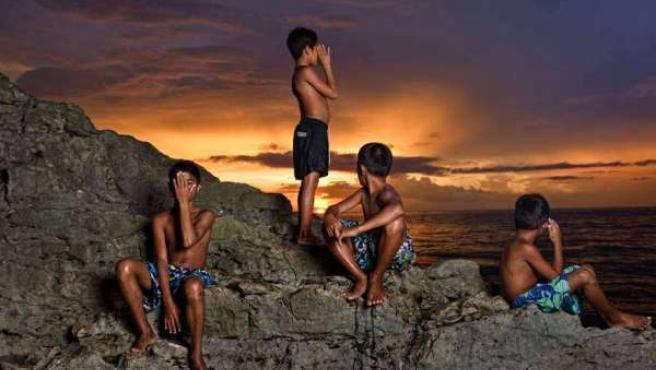 Niños asiáticos posan al atardecer en Puerto Galera, Filipinas, un paraíso natur