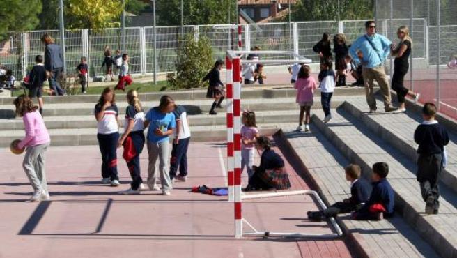 Unos niños juegan al balón en el recreo del colegio.