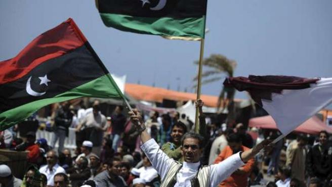 Un grupo de libios ondean banderas pre-Gadafi durante los rezos del mediodía del viernes.