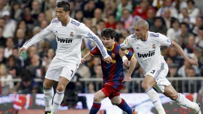 Cristiano Ronaldo, delantero del Real Madrid, se lleva el balón seguido por su compañero Pepe y por Leo Messi, del Barcelona.