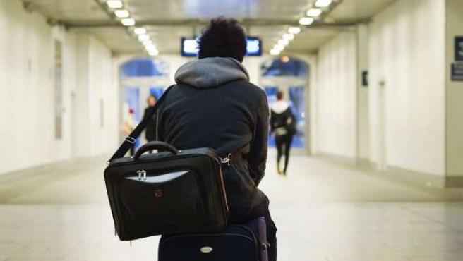 Un joven, sentado sobre su maleta en un aeropuerto.