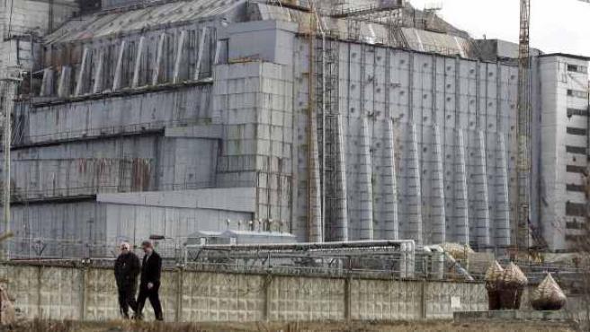 Dos trabajadores caminan junto al reactor 4 de la planta nuclear de Chernóbil (Ucrania) en una imagen de archivo del 31 de marzo de 2006.