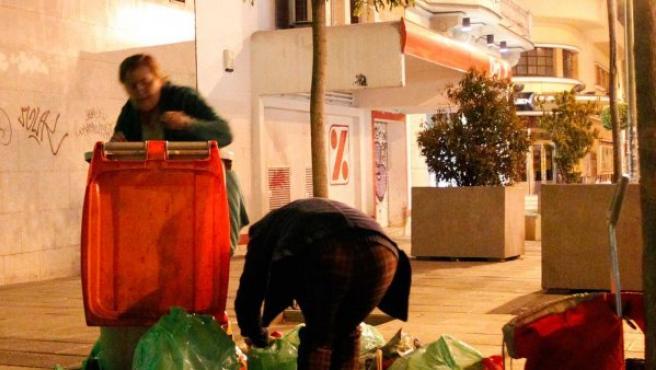 Personas buscan comida en los cubos de la basura de un supermercado.