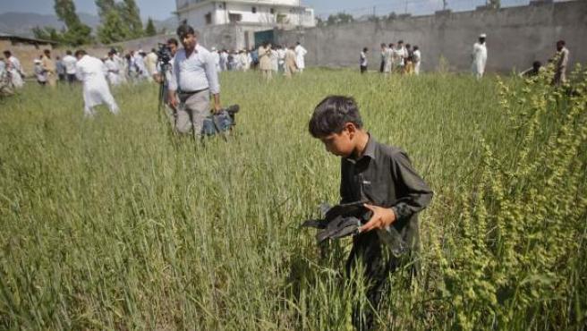 Un niño recoge los restos de un tiroteo, junto a periodistas que graban el complejo, donde el líder de Al Qaeda, Osama bin Laden, fue abatido por las fuerzas armadas estadounidenses.