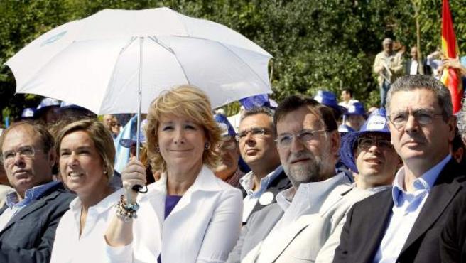 El presidente del PP, Mariano Rajoy, acompaña a la presidenta de la Comunidad de Madrid, Esperanza Aguirre, y al alcalde de la capital, Alberto Ruiz Gallardón, durante un acto del PP.