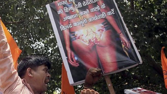 Seguidores de la organización hindú Vishwa Hindu Parishad (VHP) y del partido Bajrang Dal, sostienen una pancarta con la imagen de una modelo luciendo un traje de baño con estampados de una diosa hindú llamada Lakshmi.