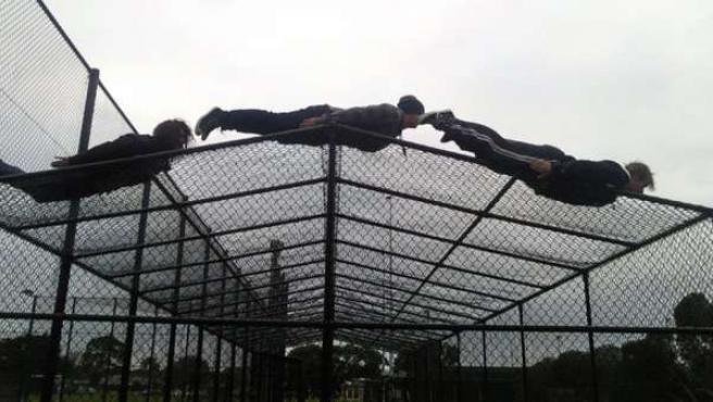"""Tres jóvenes australianos haciendo """"planking"""" sobre un tejado de alambre."""