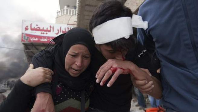 Un palestino herido es escoltado durante los enfrentamientos entre manifestantes palestinos y las fuerzas de seguridad israelíes en la ciudad de Ramala.