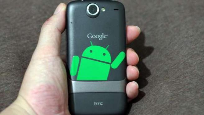 Un hombre sujeta un móvil Android.