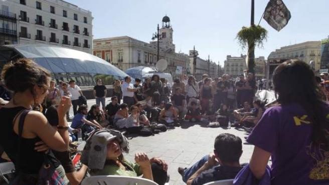 El medio centenar de jóvenes acampados en la Puerta del Sol de Madrid, que continúa con las protestas del domingo, se reúnen en una asamblea.