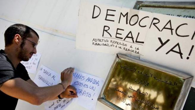 Un hombre colgando carteles de protesta a favor del movimiento 15-M en la entrada del Consulado General de España en Rabat, Marruecos.