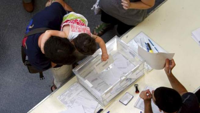Un niño introduce el voto de su padre en un colegio del barrio de les Corts de Barcelona en la elecciones municipales.