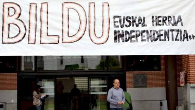 El presidente del PNV de Guipúzcoa, Joseba Egibar, pasa bajo una pancarta de apoyo a Bildu tras ejercer su derecho al voto en San Sebastián.
