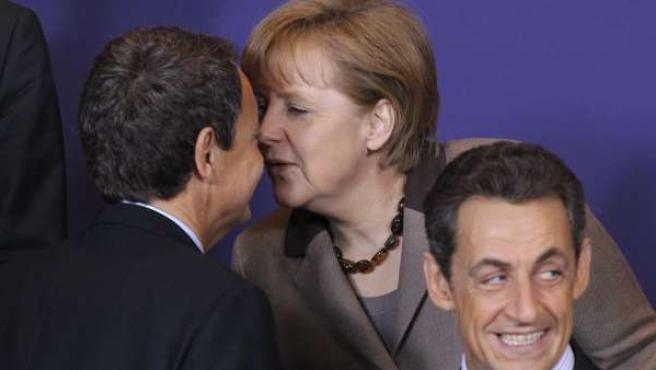 El presidente del Gobierno español, José Luis Rodríguez Zapatero, saluda a la canciller alemana Angela Merkel, junto al presidente francés Nicolas Sarkozy, antes de una foto de familia de los asistentes a una cumbre especial de la Unión Europea.