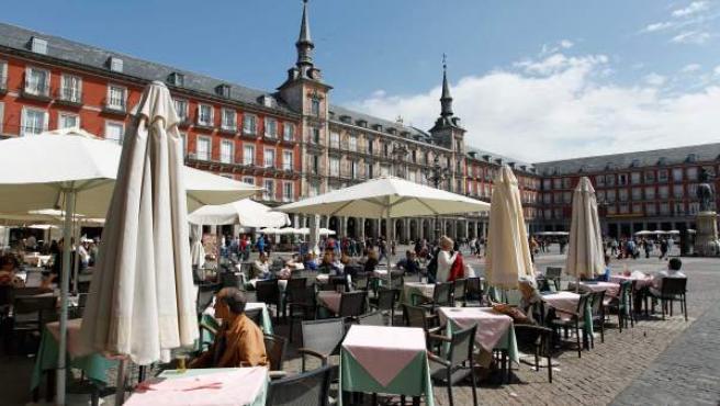 Varias personas en una terraza en la Plaza Mayor de Madrid.