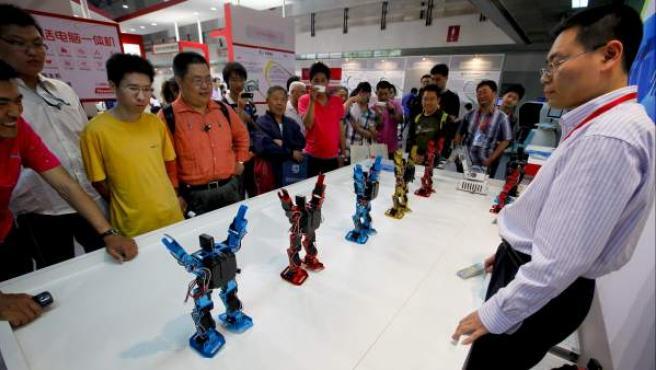 Visitantes asistiendo a una demostración de los robots 'Senpower' durante la 14ª edición de la Feria Internacional de Tecnología 'Chitec', en Pekín (China).