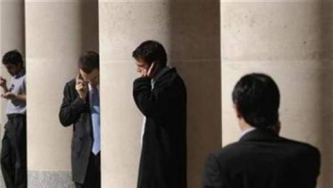 Varios trabajadores hablan por el móvil durante una pausa.