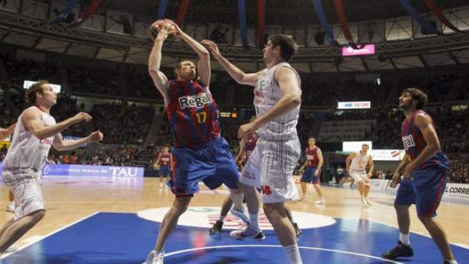 El pívot del Regal FC Barcelona, Fran Vázquez (2i), defiende el balón bajo la canasta ante la defensa del pívot croata del Caja Laboral Baskonia, Stanco Barac (2d), y del base brasileño del equipo vitoriano Marcelinho Huertas (i).
