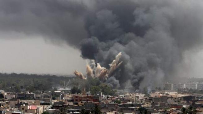 Columnas de humo se elevan sobre un barrio de Trípoli, Libia, tras un ataque aéreo de la OTAN.