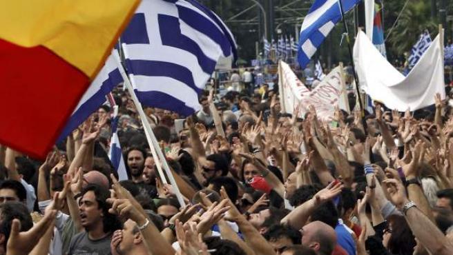 Multitud de manifestantes ondean banderas frente al Parlamento griego, en Atenas.