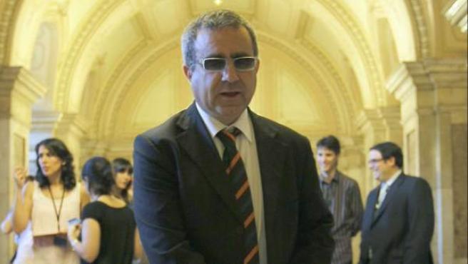 El diputado ciego de CiU, Josep María Llop, en los pasillos del Parlament con su perro, donde ha dado su versión sobre los hechos.