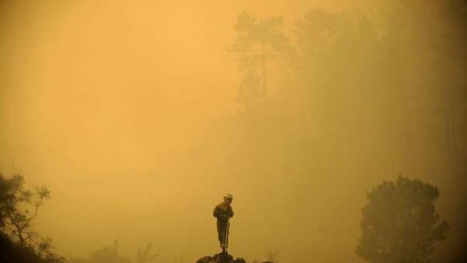 Members of the fire Galician brigade are seen around the area where a fire burns
