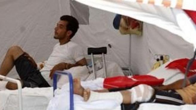 Un hombre sirio herido habla con un hombre en un tienda médica junto a un campamento de refugiados en la ciudad de la frontera turca Yayladagi, en la provincia de Hatay.