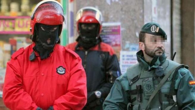 Un guardia civil y dos ertzainas custodian un inmueble de Bilbao en el marco de la operación que ha llevado a la detención de cuatro presuntos miembros de ETA a los que acusa de participar en el atentado contra el inspector de Policía Eduardo Puelles, asesinado por la banda el 19 de junio de 2009 en Arrigorriaga (Vizcaya).