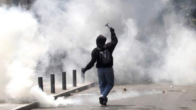 Un manifestante se enfrenta a policías antidisturbios en Atenas.