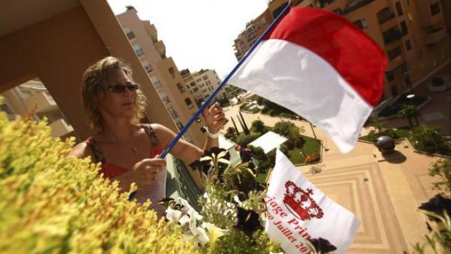 Una mujer coloca una bandera del principado de Mónaco y otra de la boda real para celebrar el enlace del príncipe Alberto II de Mónaco su prometida Charlen Wittstock.