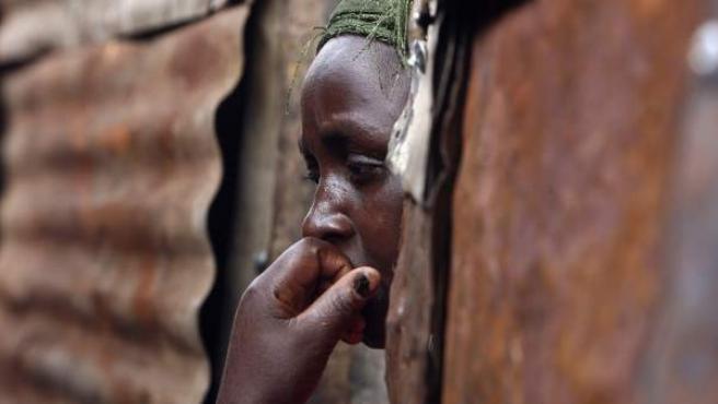 Imagen de archivo de una mujer en la puerta de una chabola de Nairobi, en Kenia.