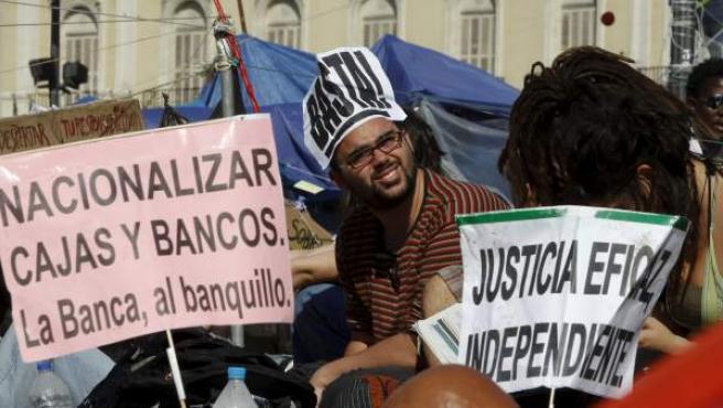 Dos jóvenes muestran varios carteles durante la concentración organizada en la madrileña Puerta del Sol.