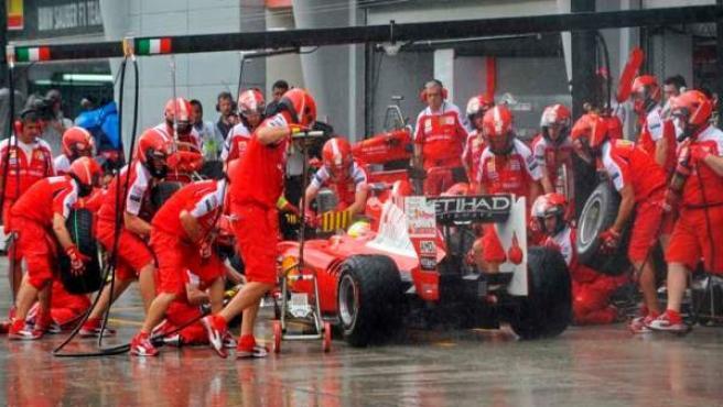 Los mecánicos de Ferrari cambian los neumáticos a un F-10.