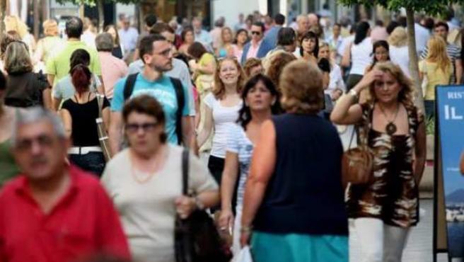Decenas de personas caminan por la calle.