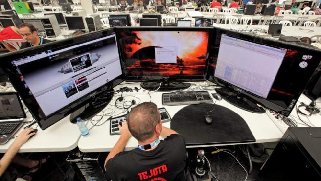 """Un hombre navega con su ordenador preparado con tres pantallas de 37"""" que le permiten disfrutar mas intensamente de los juegos."""