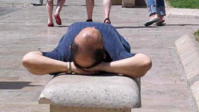 Un hombre se echa la siesta en un banco público.