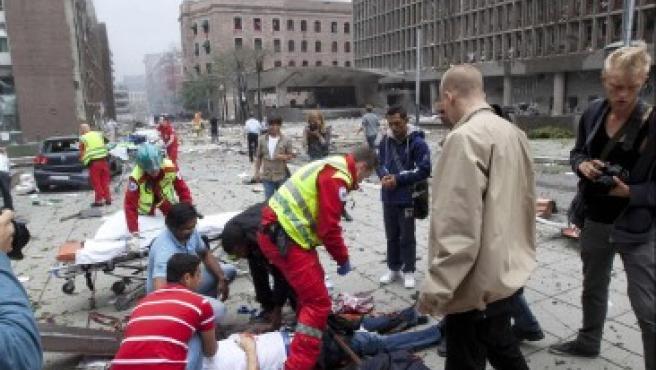 Una fuerte explosión sacudió este viernes el distrito gubernamental de Oslo y provocó varios muertos y decenas de heridos. En la imagen, los equipos de rescate atienden a los heridos en la atentado, que se ha registrado en el centro de la ciudad.