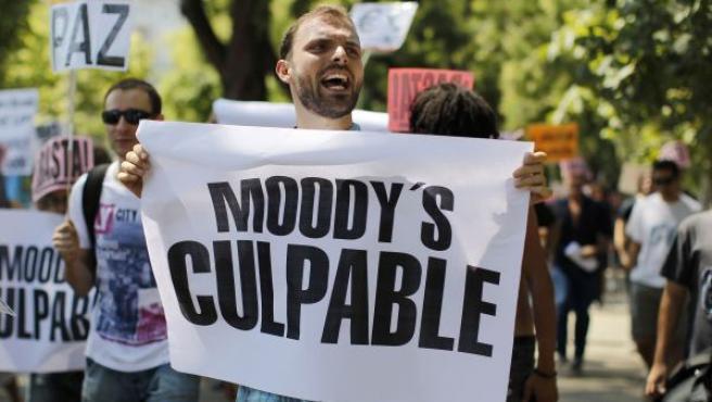"""Un manifestante del movimiento 15-M camina con una pancarta en la que se puede leer """"Moody's, culpable""""."""