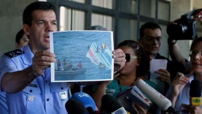 Imagen de archivo que muestra a un oficial de la Fuerza Aérea de Brasil, enseñando una foto con los primeros restos que se localizaron del avión siniestrado.