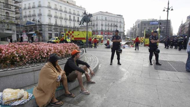 """El desalojo de los acampados desde el 23 de julio en la Puerta del Sol, en Madrid, se ha llevado a cabo de forma """"tranquila"""", según fuentes de la Policía. Sin embargo, algunos indignados aseguran que los agentes les """"pisaron"""" los pies para despertarlos."""