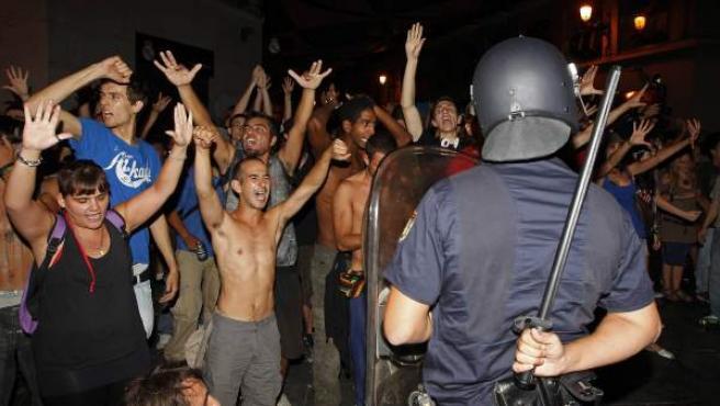 Un grupo de personas del movimiento 15-M gritan ante la Policía durante su protesta.
