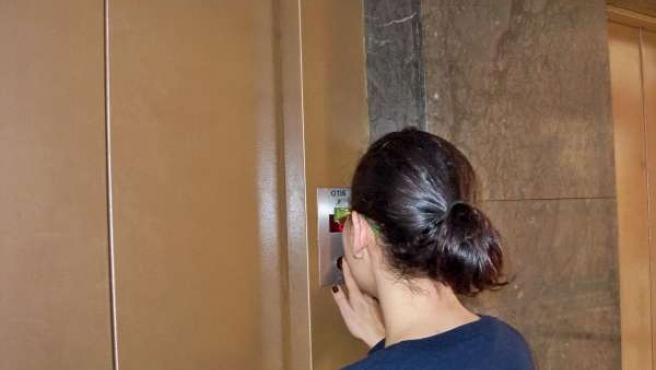 Una joven utiliza el ascensor.