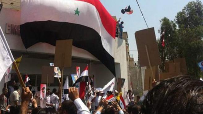 Seguidores del presidente sirio Bashar al Assad colocando una bandera siria en la entrada de la embajada estadounidense de Damasco, Siria, en una imagen de archivo.