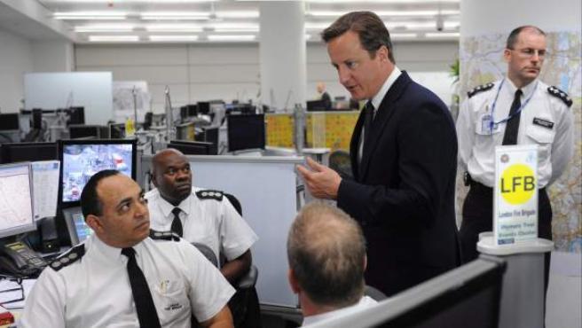 El primer ministro británico, David Cameron (segundo por la derecha), conversa con oficiales del departamento de bomberos londinense durante una visita al cuartel general del 'Comando Oro' de la Policía Metropolitana en Lambeth, sur de Londres (Reino Unido).